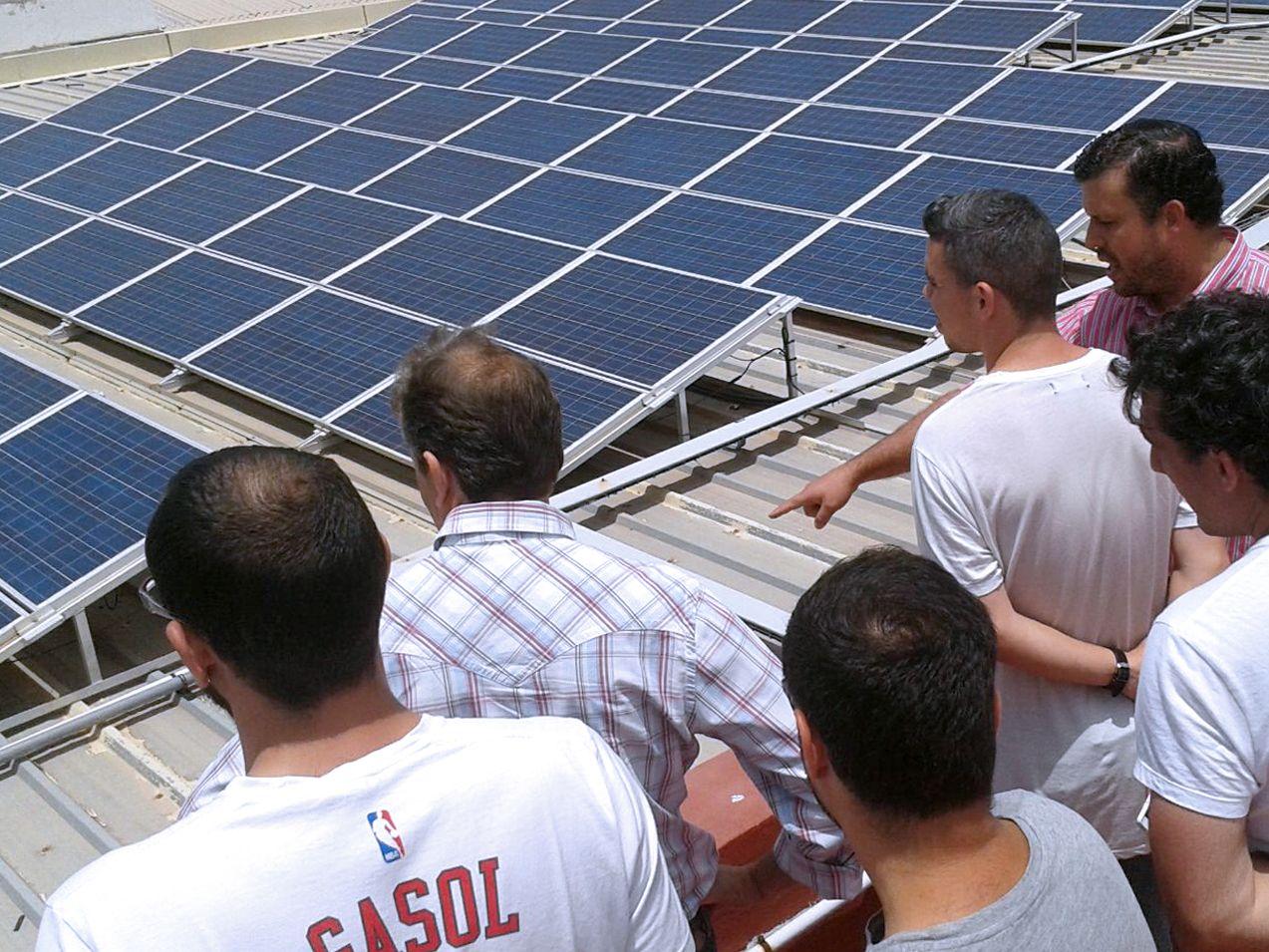 Alumnos junto al profesor estudiando una instalación solar fotovoltaica