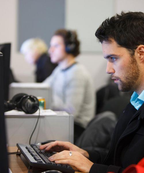 Joven frente al ordenador en su puesto de trabajo, compaginando formación con la actividad laboral